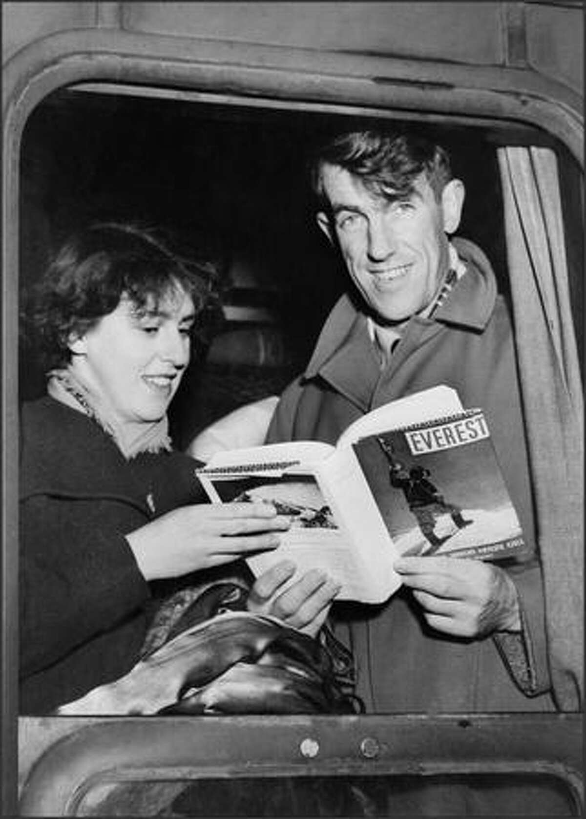 Sir Edmund Hillary and his wife Louise display in January 1954 a book about his victory over Mt. Everest as they arrive by train in Val D'Isere.