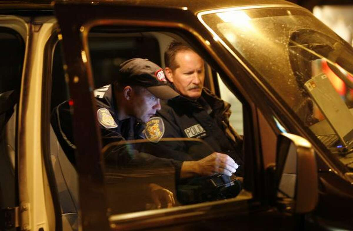 Seattle police officers and Neighborhood Corrections Initiative crew members Randy Jokela, left, and Vic Maes run a suspects name about 4:30 a.m. in Belltown.