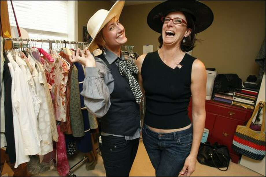 Founder of LifeStyled, Darcey Howard, left, and Michele Bayle-Zeman model some hats as they go through Bayle-Zeman's wardrobe. Photo: Meryl Schenker/Seattle Post-intelligencer Photos