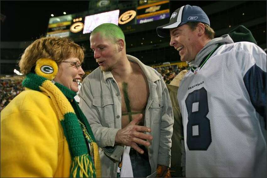 Deborah Schnider, from Winthrop Harbor, Illinois, and Ray Howll, wearing a painted #4 on his chest, from Burlington, Wisconsin, reserve comment on Glen Kanenwisher's jersey choice during a Packer pep rally held at Lambeau Field in Green Bay, Wisconsin. Kanenwisher is a Boeing manager from Seattle who is celebrating his 46th birthday at Lambeau Field.