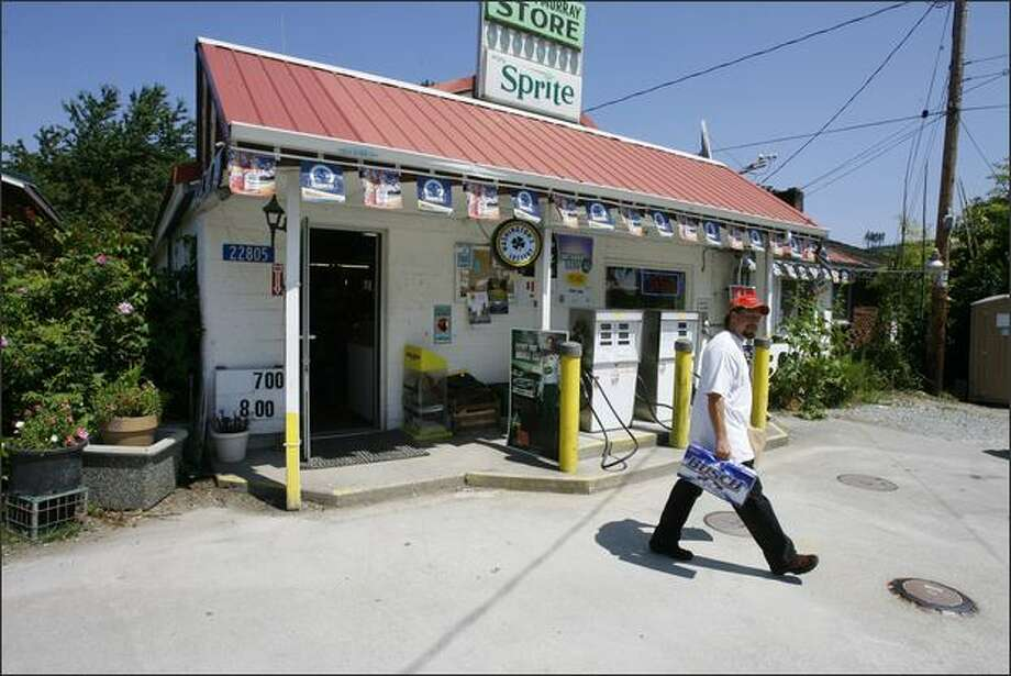 A customer leaves Lake McMurray Store, where gasoline comes from two old pumps, the kind with dials that turn, rather than digital readouts. Photo: Gilbert W. Arias/Seattle Post-Intelligencer