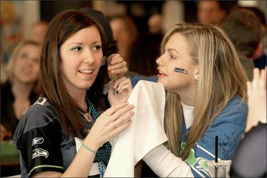 Lauren Lewicki and Emily Schnoor apply Hawks tattoos at F.X. McRory's Whiskey Bar.