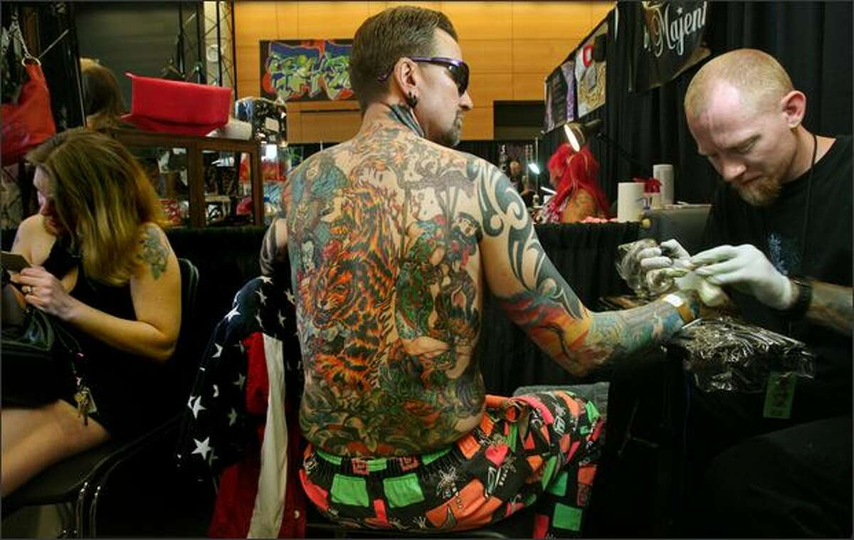 Tattoo artist Lance Dozier of Electra Tattoo of Marysville applies color to a dragon tattoo on Ed Scoll, also of Marysville, at the 7th Annual Seattle Tattoo Expo. Dozier has done all of Scoll's body art, a process that began more than six years ago. See more photos.