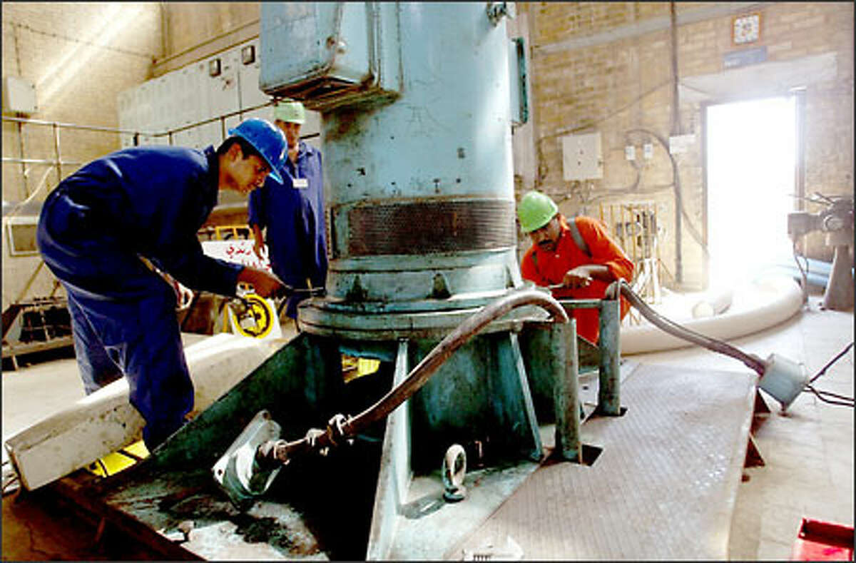 Water-treatment workers work on a motor for a pump at a project in Rastama, Baghdad. War damage has affected water quality in Iraq.