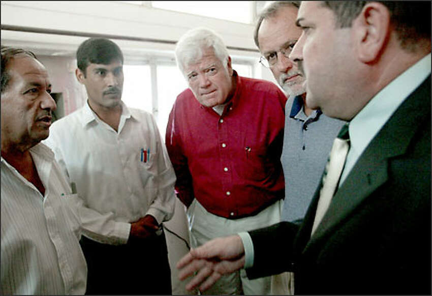 Reps. Jim McDermott, D-Wash., center, and David Bonior, D-Mich., second from right, listen to a plant manager at the water-treatment project in Rastama, Baghdad. Many treatment plants have not been repaired.