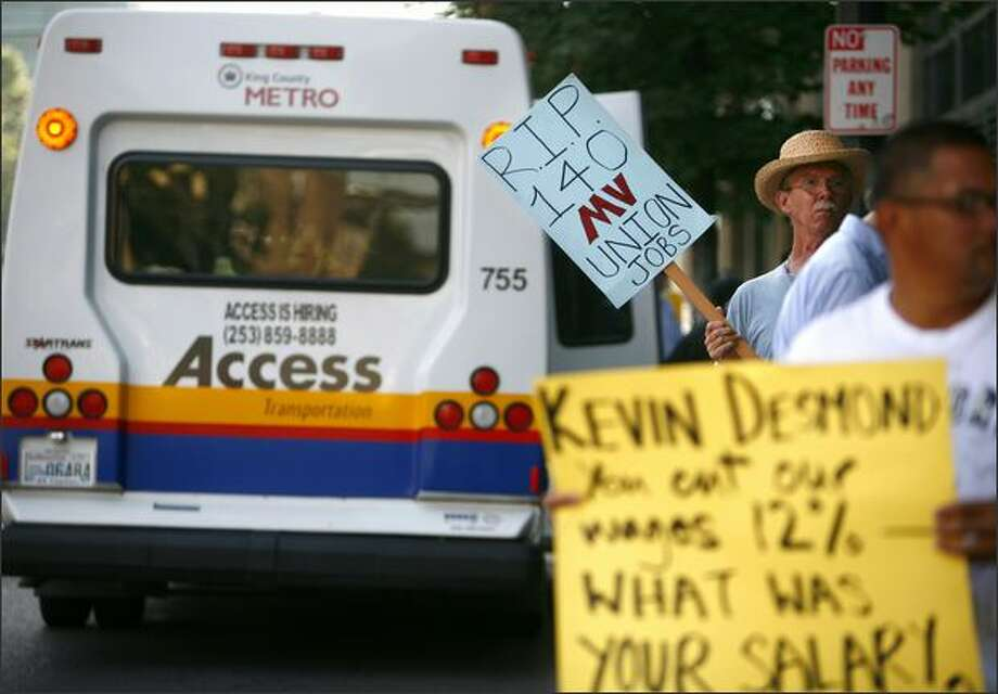 Access bus driver Larry Drake, in hat, holds a sign during an informational picket in downtown Seattle as one of the buses driven by Access drivers makes a stop. Photo: Joshua Trujillo/Seattle Post-Intelligencer