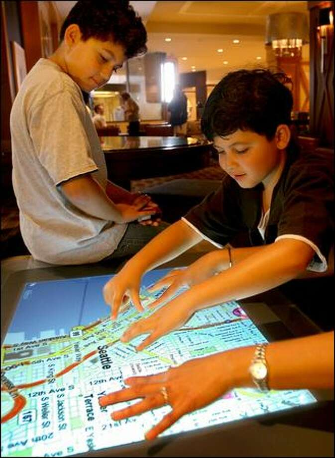 Brothers Sam, 9, left, and Mathew Moesinia, 7, of Beverly Hills, Calif., check out a view of downtown Seattle with the help of Vanessa Lee (arms showing) of Microsoft Corp. Selected Sheraton Hotels, including the downtown Seattle Sheraton, are debuting Microsoft's Surface tabletop computers starting Wednesday. At guests' fingertips are 360-degree satellite maps and tools to search for local attractions and services. Photo: Scott Eklund/Seattle Post-Intelligencer