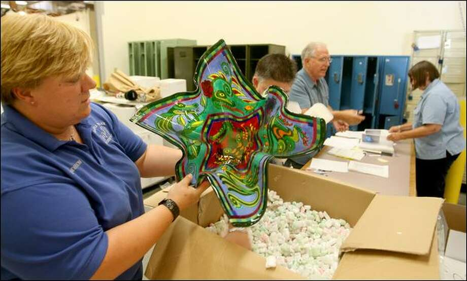 Susan Anderson of the Seattle Police Evidence Unit checks out glass artwork Wednesday at the department's evidence facility. Photo: Scott Eklund/Seattle Post-Intelligencer