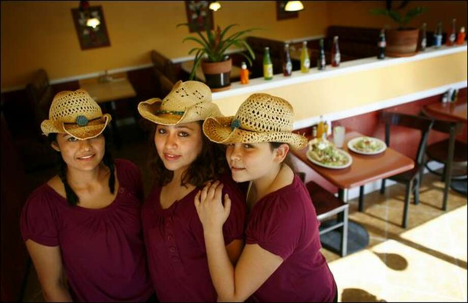 Carmen Alejo, center, with her sister Jasmin Alejo, right, and waitress Miligol Cruz work in Alcatraz Mexican Restaurant in Rainier Valley, which Carmen Alejo opened in June. The 23-year-old is hoping the restaurant will help improve the neighborhood she grew up in. Photo: Joshua Trujillo/Seattle Post-Intelligencer