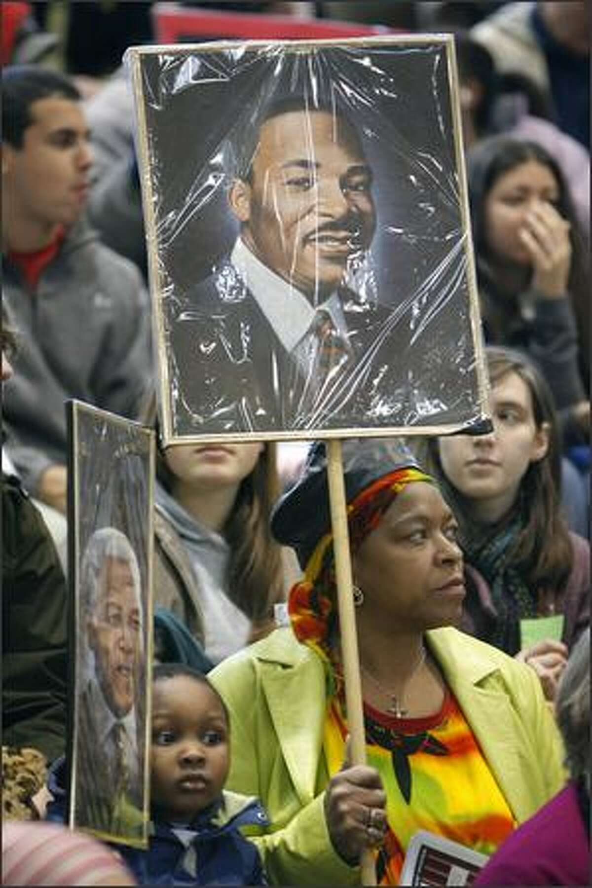Davon Fuller holds a photo of Nelson Mandela as he squeezes in beside his grandmother, Fai Mathews, who holds a poster of Martin Luther King Jr. in the gym at Franklin High School on Monday. (Photo/Seattle Post-Intelligencer, Gilbert W. Arias)