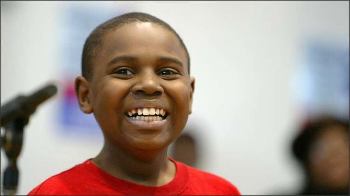 Isiah Barnett is all smiles as he soaks up the applause after reading a poem at Franklin High School during the Martin Luther King Jr. Day celebration. (Photo/Seattle Post-Intelligencer, Gilbert W. Arias)