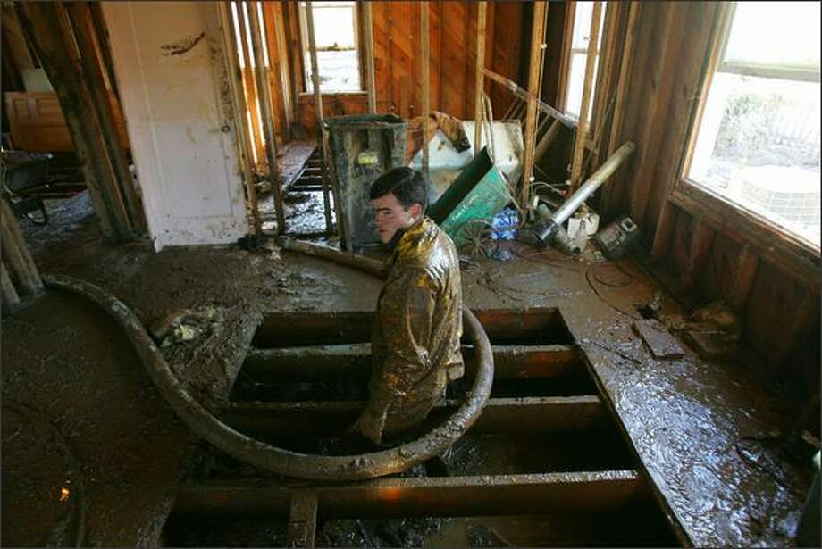 Dwight Martin, 22, a Mennonite volunteer from Rochester, Wash., stands in the mud-laden crawl space of Lewis County resident Steve Roberts' home in Curtis, Wash. He and four other young Mennonite men are helping Roberts, and other Lewis County residents, clean up and dry out after major flooding last December. Photo: Mike Kane, Seattle Post-Intelligencer