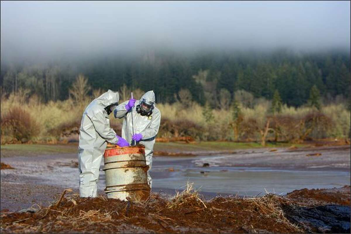 Department of Ecology hazardous spill responders John Hanson, left, and Ron Holcomb test the toxicity of a barrel drum found in a formerly flooded field on River Road near Adna, Wash.