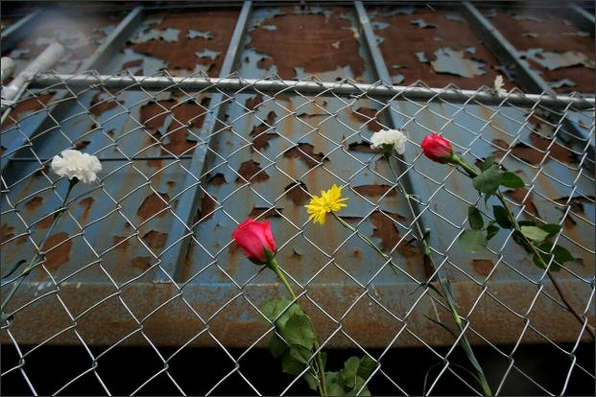 Flowers line the fence in memoriam in front of the old Rainier Cold Storage building.