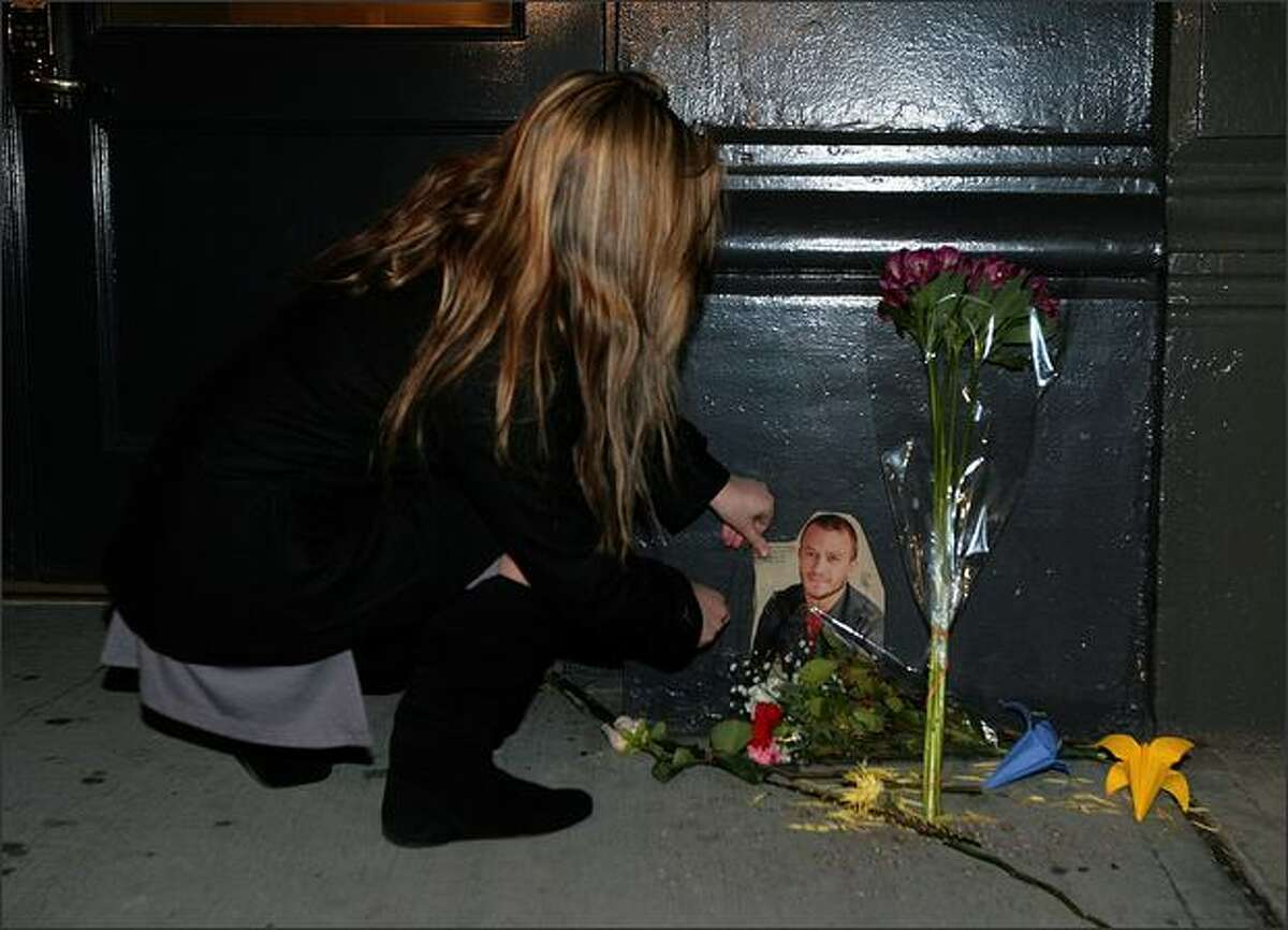 Jennifer Rosner, 21, places a photo of the late actor Heath Ledger at a makeshift memorial outside the building where his body was found. (AP Photo/Gary He)