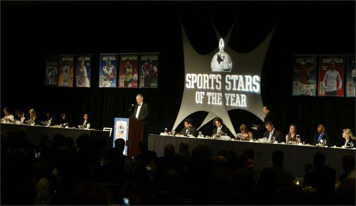 Master of ceremonies Steve Raible, center, stands at the podium in front of the head table during the 73rd Seattle Post-Intelligencer Sports Star of the Year Awards held at the Westin Hotel.