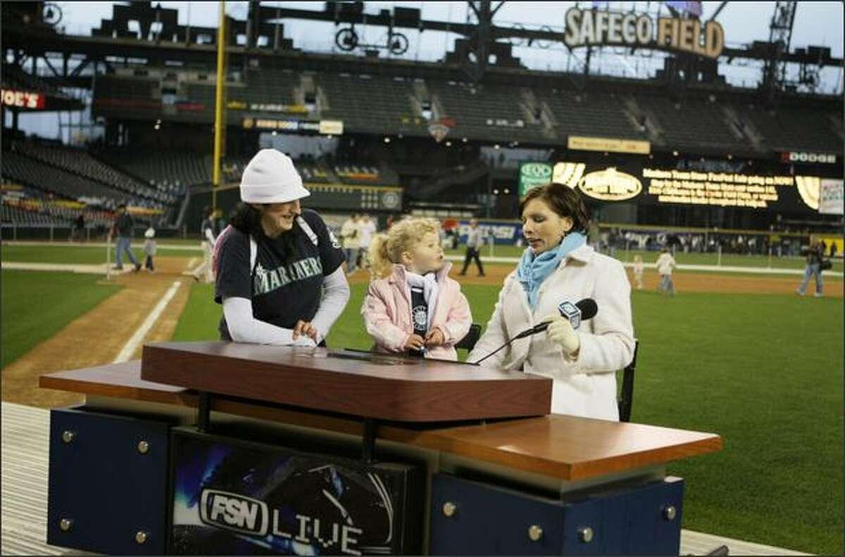 Sara Roulston (left) and her goddaughter Laeden Snyder, 3, of Mukilteo, speak with Jen Mueller of Fox Sports Northwest, right.