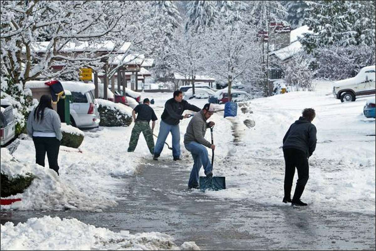 Residents of Martha's Landing Condominiums turn in a group effort to clear snow from their driveways near Martha Lake in Snohomish County.