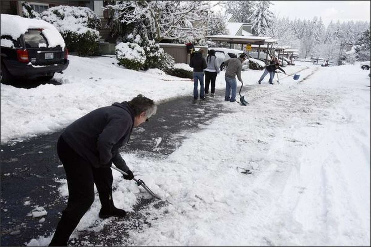 Residents of Martha's Landing Condominiums turn in a group effort to clear snow from sidewalks.