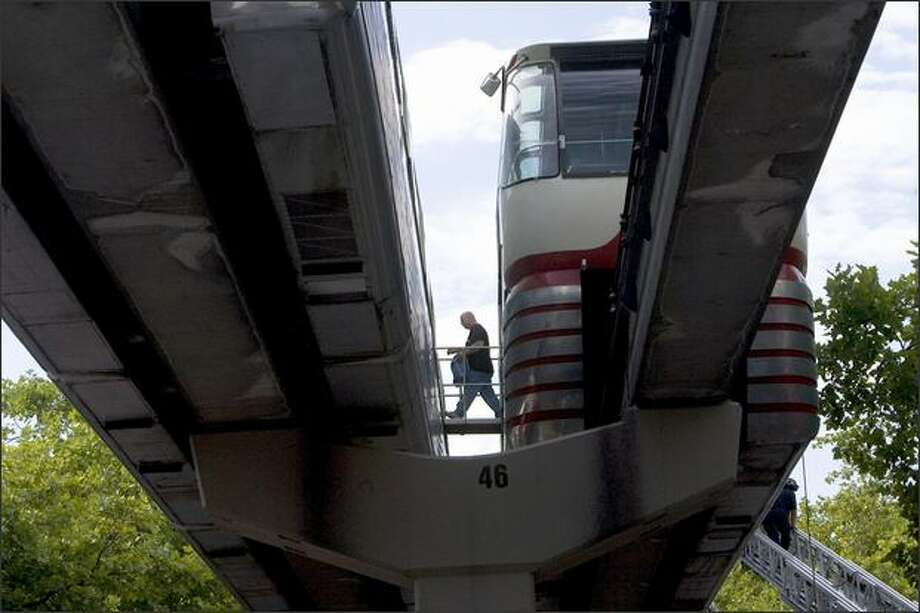A passenger cross from the red train, right, to the blue train. Photo: Grant M. Haller/Seattle Post-Intelligencer