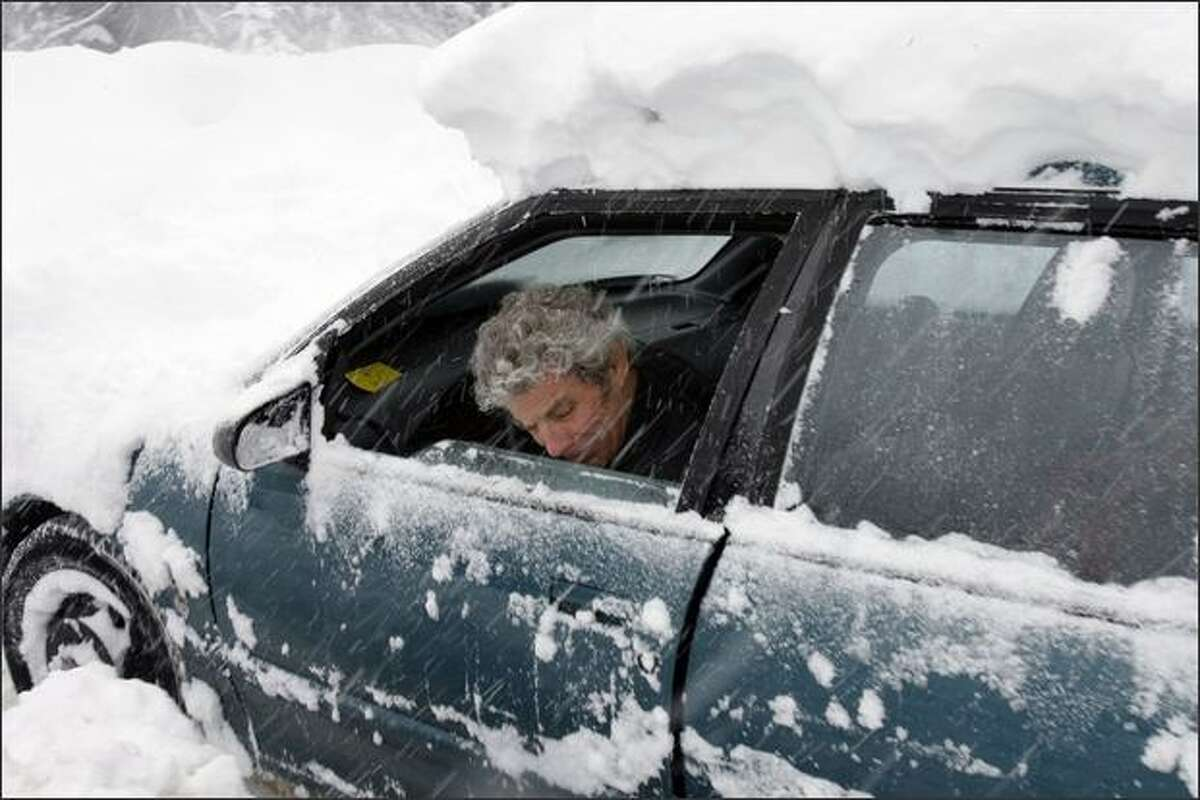 Barney Bales from the Fremont neighborhood of Seattle, tries to move his car after spending about 20-minutes digging it out from under two days of snow at Crystal Mountain Wash.