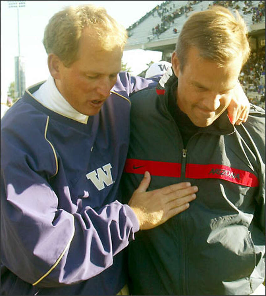 Washington head coach Rick Neuheisel, left, has a little one-on-one talk with Arizona head coach John Mackovic after the Huskies defeated the Wildcats 32-28.