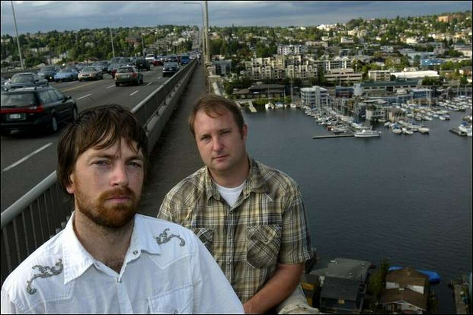 "Musicians Ethan Anderson, left, and Adam Monda of Massy Ferguson, a rock band, pose on the Aurora Bridge this week. In 2006, a friend committed suicide by jumping off the bridge. The pair wrote a song called ""The Ride,"" which is about getting past despair. Photo: Karen Ducey/Seattle Post-Intelligencer"