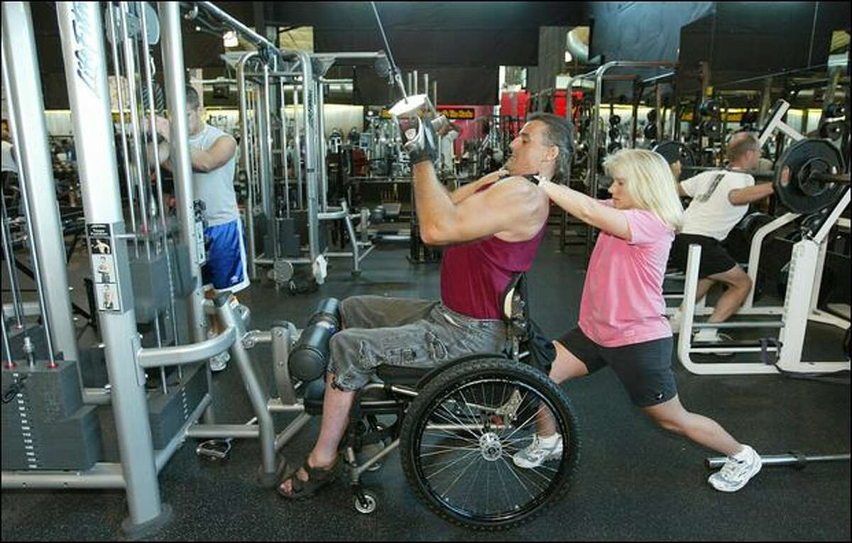 Assisted by his wife, Dani, Mike Utley works out in a Wenatchee gym. The former offensive guard and the former paramedic met while they were working out.