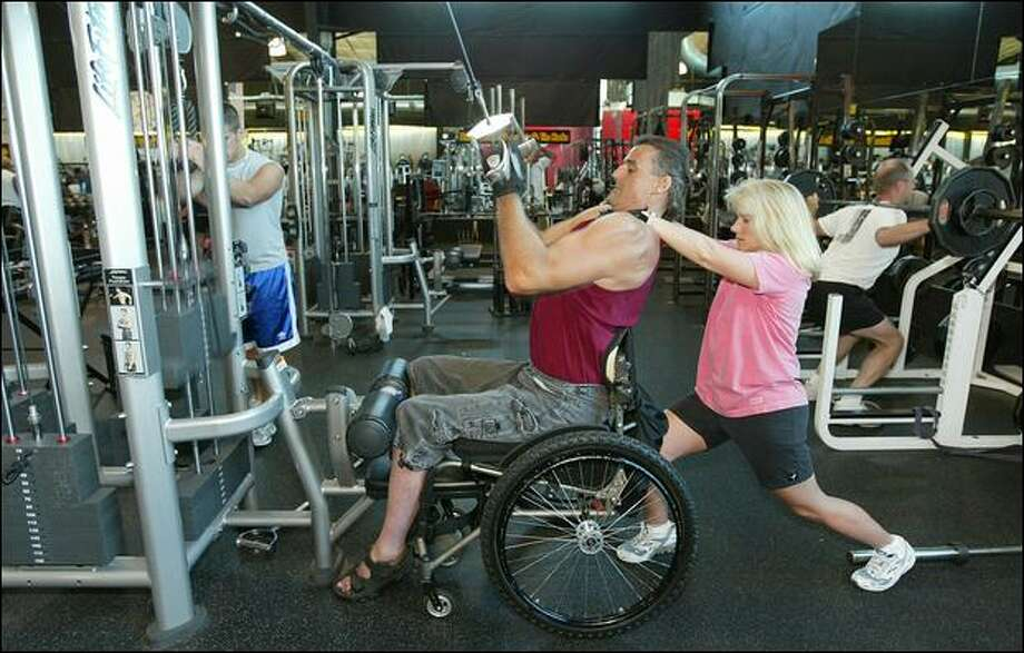 Assisted by his wife, Dani, Mike Utley works out in a Wenatchee gym. The former offensive guard and the former paramedic met while they were working out. Photo: P-i File/2006