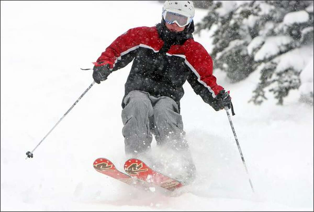 A skier cuts through powder on a double black diamond run at Crystal Mountain.