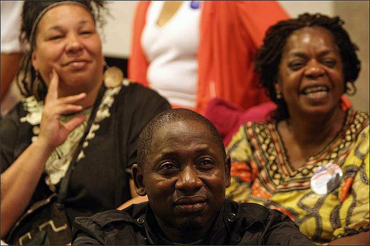 Dawn Mason, a former state representative, right, Marsha Tate, left, and Autah Apah, from Kenya, center, react to Sen. Barack Obama's nomination acceptance speech at a party Mason held at her home in South Seattle. At left is Dakari Jefferson, 10, of Spanaway.
