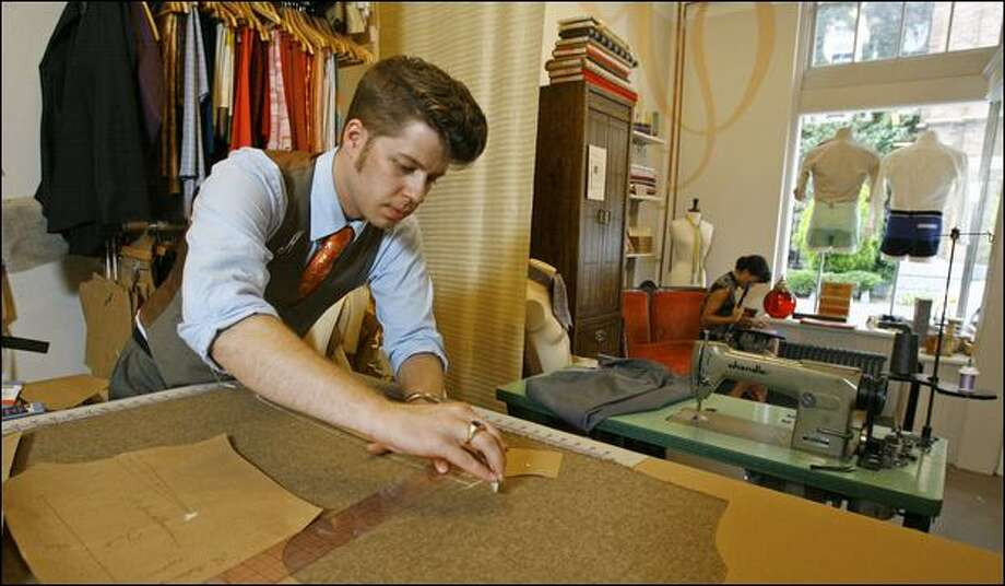 Fashion designer Michael Cepress cuts a pattern for a vest at his showroom and shop. Cepress involves his customers in the design process for their clothing. Photo: Gilbert W. Arias/Seattle Post-Intelligencer