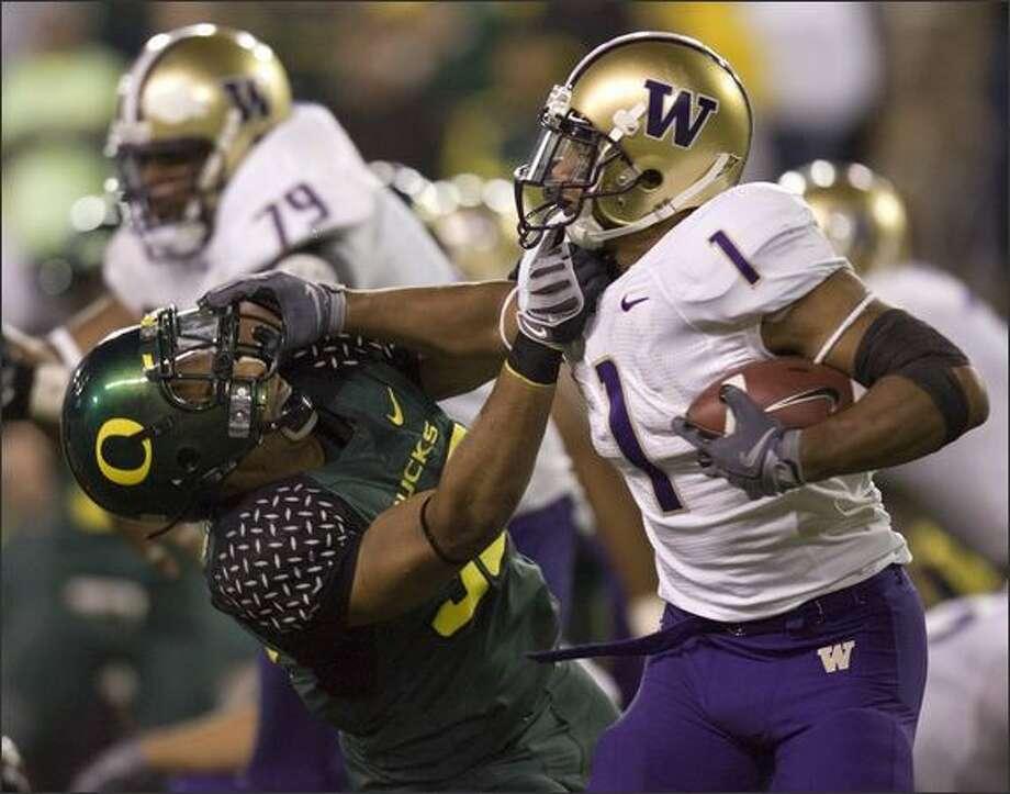 Washington tailback Chris Polk, right, battles for yardage against Oregon defender Will Tukuafu during the second half. Oregon beat Washington 44-10. Photo: / Associated Press