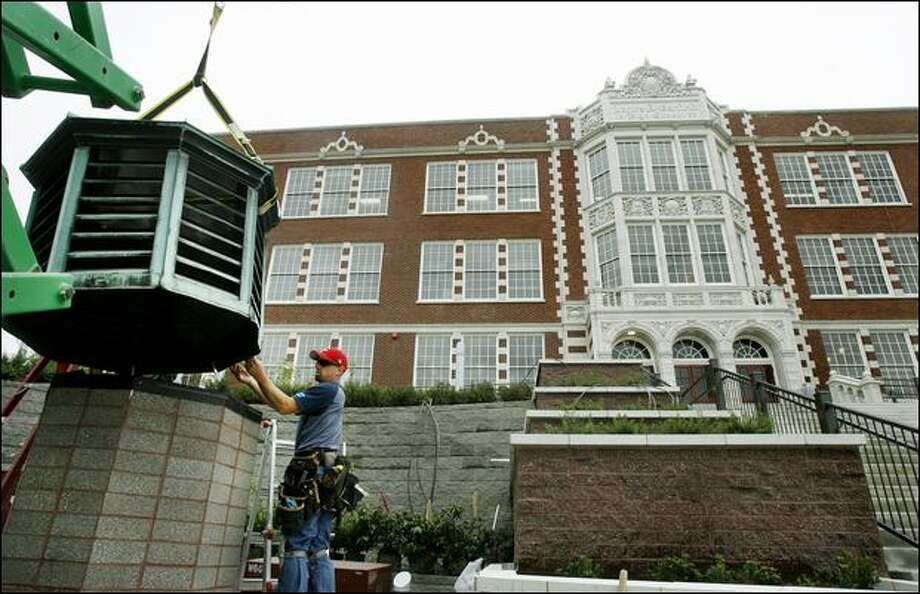 Mike Cowger of Northshore Sheet Metal Inc. of Everett helps position an exhaust vent, moved from the roof of Garfield High School, into position to serve as a lighting fixture outside the newly renovated school. The $107 million renovation is the most expensive attempted by Seattle Public Schools. Photo: Dan DeLong/Seattle Post-Intelligencer