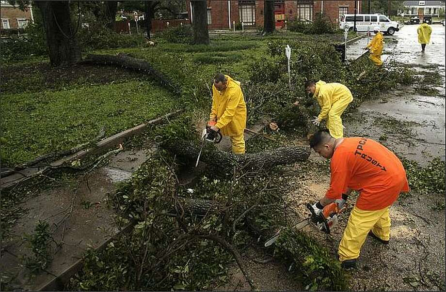 Workers clean up debris left by Hurricane Gustav Monday in Houma, La. A weaker-than-expected Hurricane Gustav swirled into the fishing villages and oil-and-gas towns of Louisiana's Cajun country Monday, delivering only a glancing blow to New Orleans. Photo: / Associated Press