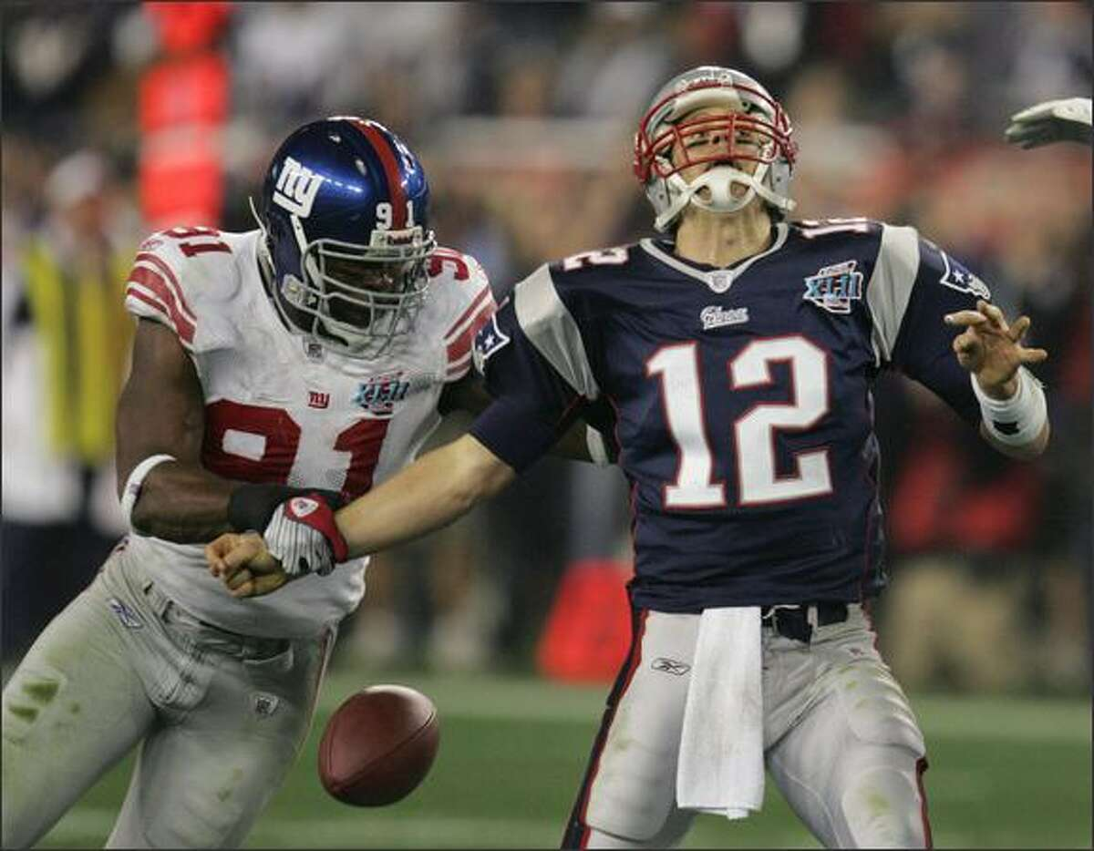 New York Giants defensive end Justin Tuck strips the football from New England Patriots quarterback Tom Brady during the second quarter of Super Bowl XLII.