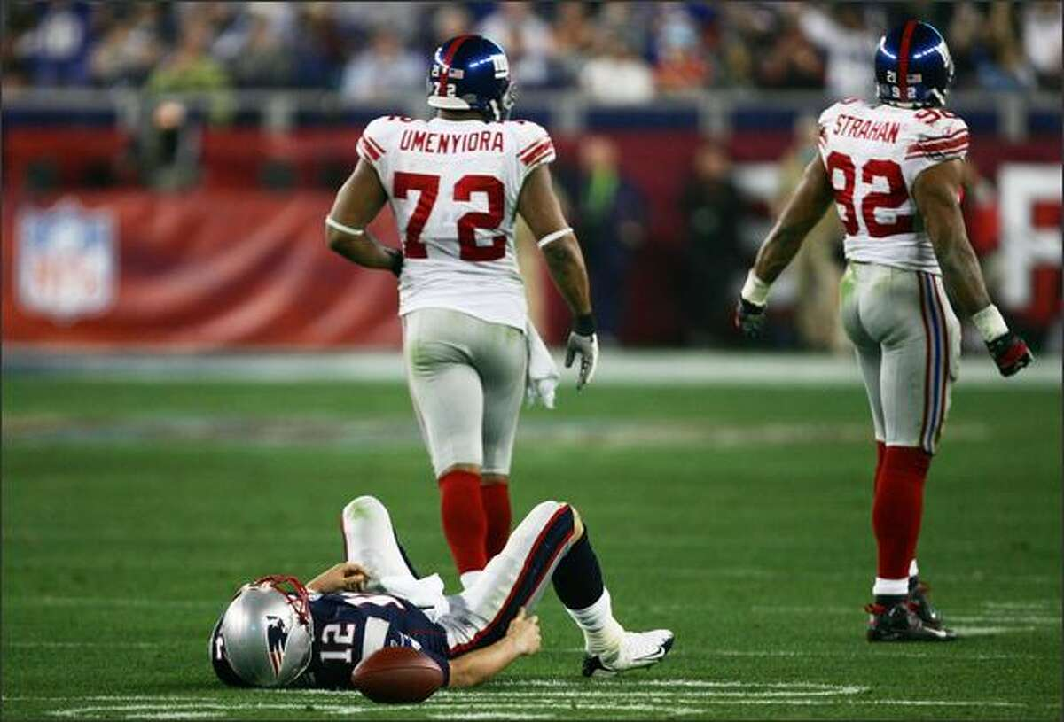 Quarterback Tom Brady of the New England Patriots lies on his back after being sacked by defensive end Michael Strahan #92 of the New York Giants in the third quarter during Super Bowl XLII.