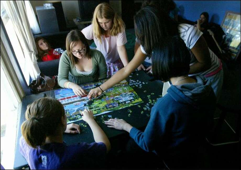 Susie Wright, 14, center, and Izzy Bonser, 11, work on a puzzle Monday at the Boys & Girls Club in Bellevue. The club is extending its hours to accommodate those affected by the Bellevue teachers strike. Photo: Karen Ducey/Seattle Post-Intelligencer