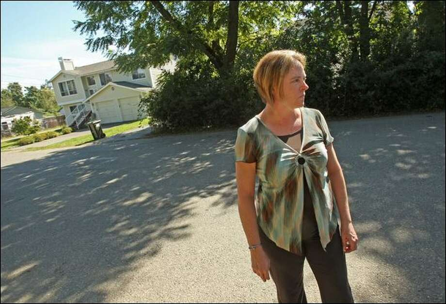 Dawn Lambe stands in the street that passes between her house and the house, at left, where a 71-year-old woman was attacked Monday by a pair of free-roving pit bulls in SeaTac. Lambe's father, Henry Hall, who lives next door to Lambe, saw the attack, called police and helped get the dogs off the victim. Photo: Mike Kane/Seattle Post-intelligencer Photos