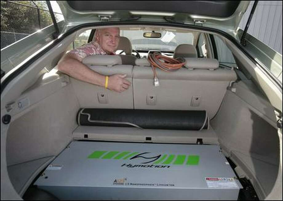 "Dan Davids of Woodinville had this lithium battery installed in his Toyota Prius. It is located where the spare tire would go. Davids and Hymotion, the company that makes the battery, said it doubles the miles per gallon from 50 to 100. ""I can go 1,000 miles on a regular (10-gallon) tank of gas,"" Davids says. Photo: Meryl Schenker/Seattle Post-Intelligencer"