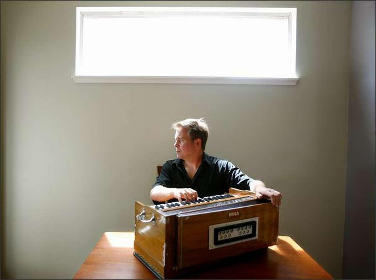 Garrett Fisher playing the harmonium in his Seattle home.