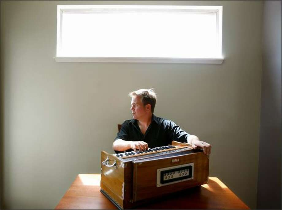 Garrett Fisher playing the harmonium in his Seattle home. Photo: Paul Joseph Brown/Seattle Post-Intelligencer