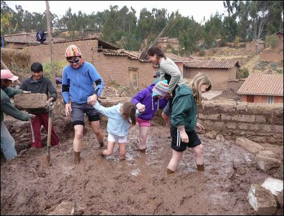 Doing their muddy best to make mortar for an orphange in Chinchero, Peru, are, from left, Sarah Mackay of Seattle, Trinity Mackay and her mom, Chris Mackay, of Seattle (no relation to Sarah), and twin sisters Alison (in hat) and Megan Heatherington of Redmond. Seattle-based Crooked Trails annually offers tours to Peru, Ghana, Nepal and other destinations. Photo: Crooked Trails