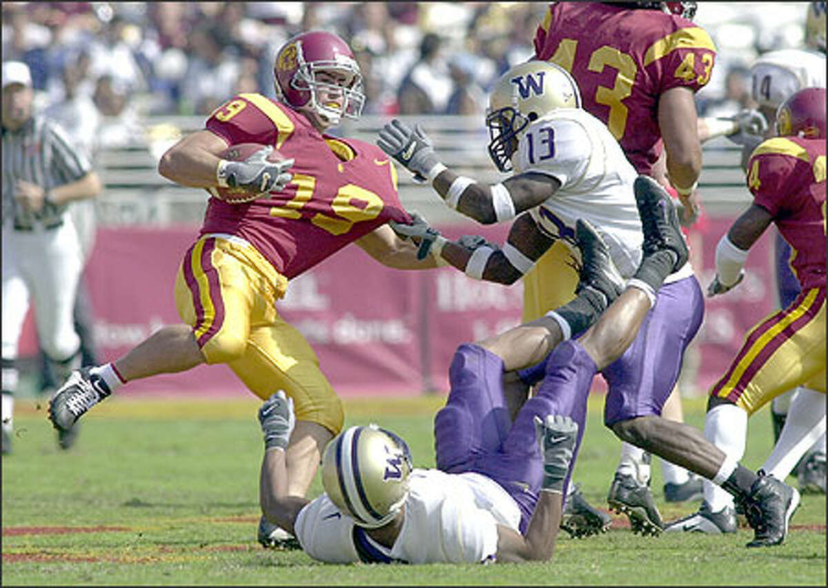 University of Washington's Nate Robinson (13) pulls on the jersey of Southern Cal's Greig Carlson (19) during the first half on Saturday, Oct. 19, 2002 in Los Angeles.