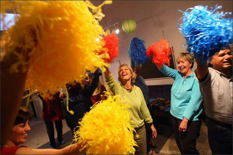 """Linda Kelly, green top, who is battling cancer, participates in a laughter yoga session at Roaring Mouse Creative Arts Studio in Northeast Seattle. """"I just think it makes sense,"""" Kelly says. """"Part of the healing process is to feel the joy in your heart."""" The sessions in silliness promise gentle aerobics, social connection and stress relief. Photo: Mike Kane/Seattle Post-Intelligencer"""