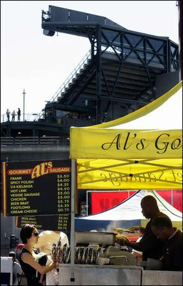 Al Griffin, owner of Al's Gourmet Sausage stand on Occidental Boulevard, serves customers before the Mariners game Wednesday afternoon at Safeco Field. Griffin, who started the stand in 1995, says that his business has slowed with the drop in attendance due to an unsuccessful Mariners season. Photo: Andy Rogers/Seattle Post-Intelligencer