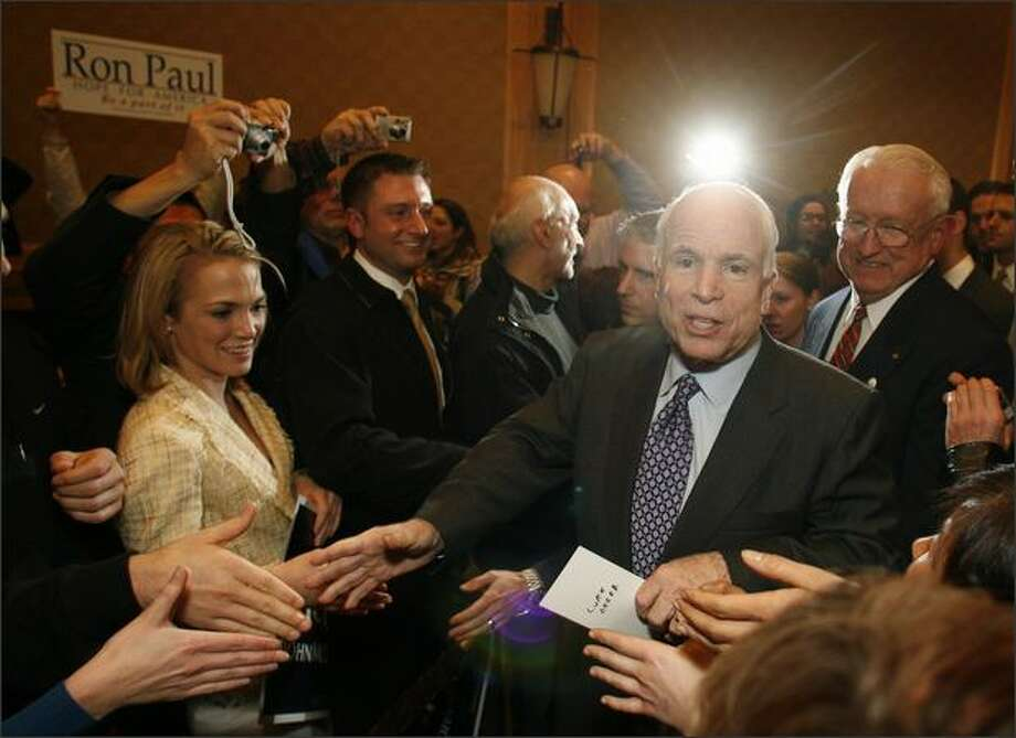 Republican presidential candidate Sen. John McCain makes his way through a receiving line as he arrives to address supporters at the Westin Hotel in Seattle. But not all were supporters as evidenced by the Ron Paul sign. Photo: Mike Urban, Seattle Post-Intelligencer
