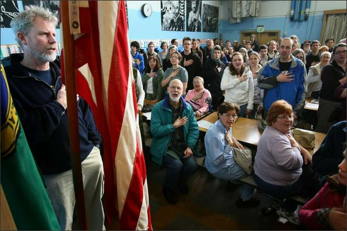 Neighborhood residents recite the pledge of allegiance during a Democratic caucus at Olympic Hills Elementary school in north Seattle.