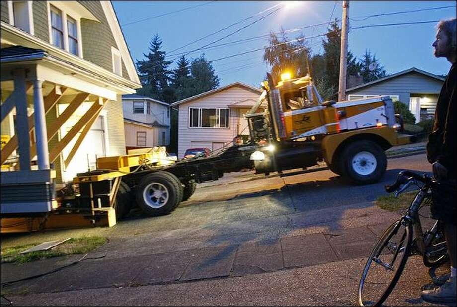 Leo Johnston watches movers pull a 100-year-old house up the steepest part of Phinney Avenue North last week on its way to a new location in Fremont. Photo: Brad Vest/Seattle Post-intelligencer Photos