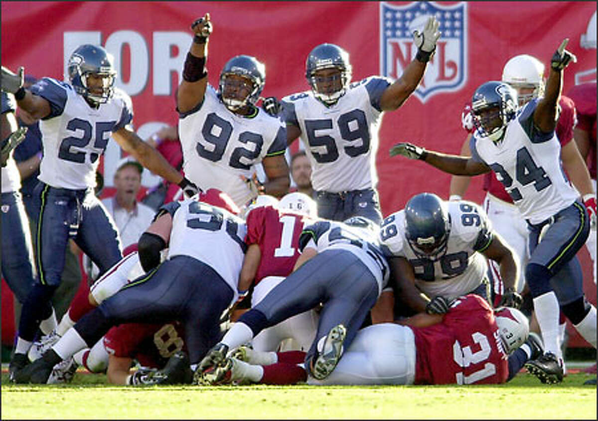 Reggie Tongue (25), Lamar King (92), Tim Terry (59) and Shawn Springs (24) indicate Seattle's possession after the Cardinals' Marcel Shipp (31) fumbled the ball during the third quarter.